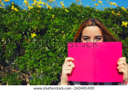 Portrait of charming young woman with pink book held up close to her face, cute female covering half face with a book while standing on spring green hedge with flowers background, filtered image - stock photo