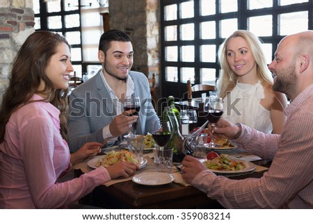 Portrait of cheerful adults having dinner in restaurant - stock photo