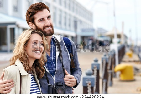 portrait of cheerful affectionate tourist couple with camera on vacation - stock photo