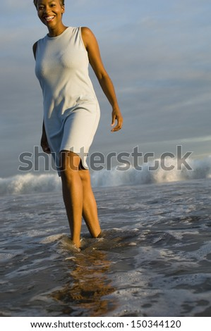 Portrait of cheerful African American woman walking through surf on beach - stock photo