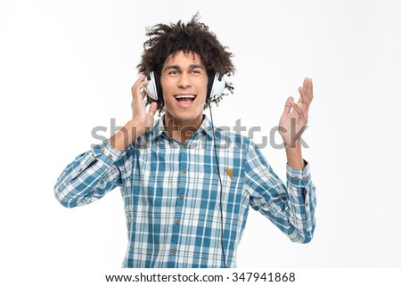 Portrait of cheerful afro american man with curly hair listening music in headphones isolated on a white background - stock photo