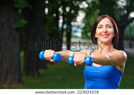 Portrait of cheerful aged caucasian smiling woman in fitness wear exercising with dumbbells in green park. - stock photo