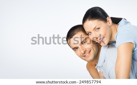 Portrait of cheerful amorous young couple, with copyspace blank area for text or slogan, against grey background