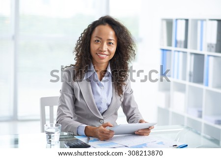 Portrait of cheerful Asian business lady with digital tablet