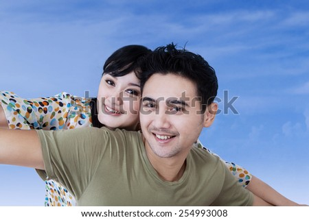 Portrait of cheerful asian couple playing together under blue sky - stock photo