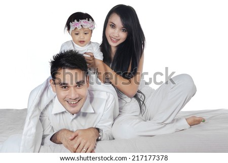 Portrait of cheerful asian family smiling at camera while playing in the bedroom - stock photo