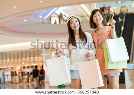 Portrait of cheerful Asian girls shopping in a mall - stock photo