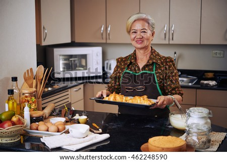 Portrait of cheerful Asian housewife with tray of fresh croissants