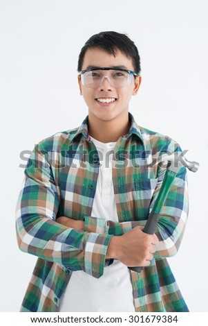 Portrait of cheerful Asian man holding claw hammer - stock photo