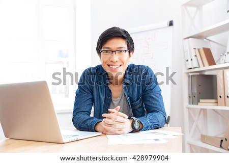 Portrait of cheerful asian young businessman working with laptop on workplace  - stock photo