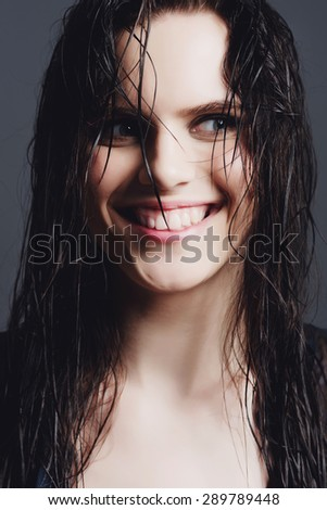 Portrait of cheerful attractive girl with wet hair in studio on a blue background - stock photo