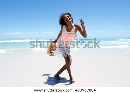Portrait of cheerful attractive young african woman enjoying walk on beach  - stock photo