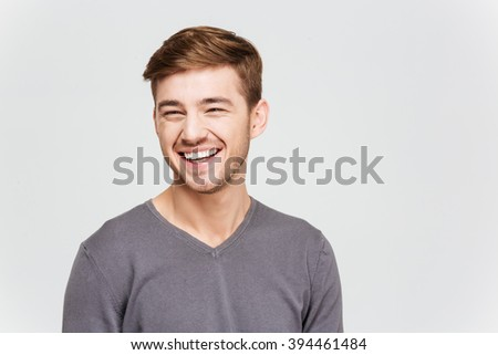 Portrait of cheerful attrative young man in grey pullover over white background - stock photo