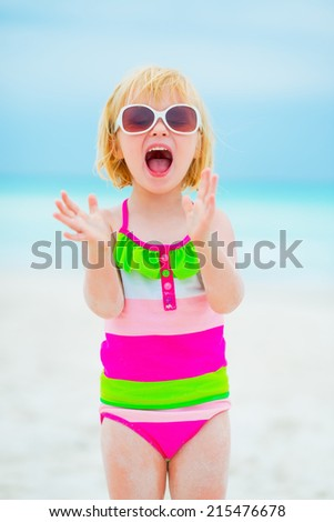 Portrait of cheerful baby girl in sunglasses on beach - stock photo