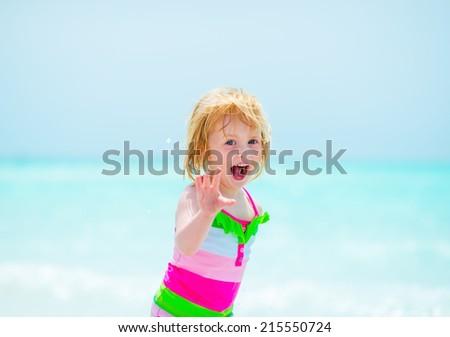 Portrait of cheerful baby girl on beach - stock photo