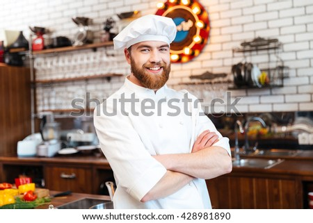 Portrait of cheerful bearded chef cook standing with arms crossed on the kitchen - stock photo