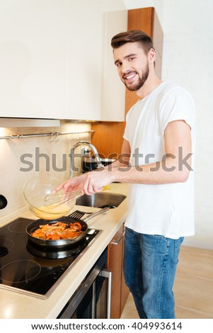 Portrait of cheerful bearded man cooking omelette on the kitchen - stock photo