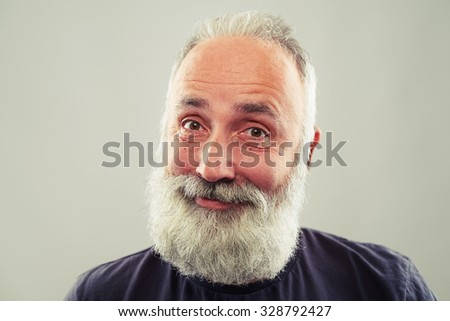 portrait of cheerful bearded man over light grey background