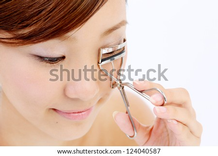 Portrait of cheerful beautiful woman making curl eyelashes using curling cosmetic tool. Over white background