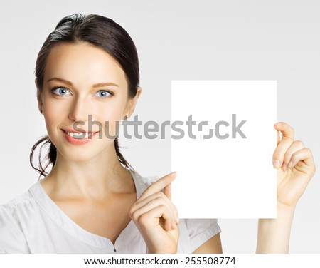 Portrait of cheerful beautiful woman showing blank signboard with copyspace area for text or slogan, over grey - stock photo
