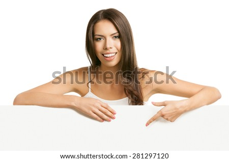 Portrait of cheerful beautiful young brunette woman in tank top casual smart clothing, pointing on empty blank signboard with copyspace area for text or slogan, isolated against white background - stock photo