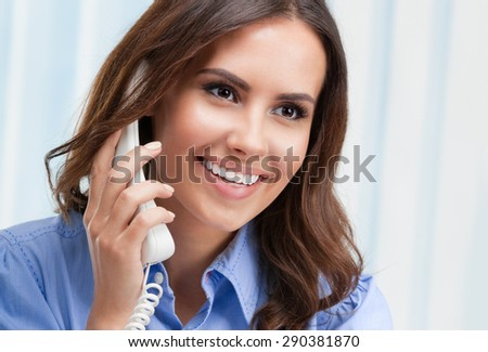 Portrait of cheerful beautiful young businesswoman or customer support female phone worker, at office. Customer assistance service concept. - stock photo