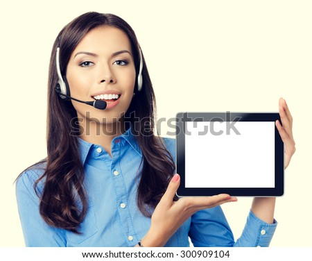 Portrait of cheerful beautiful young customer support phone operator showing blank no-name tablet pc monitor - stock photo