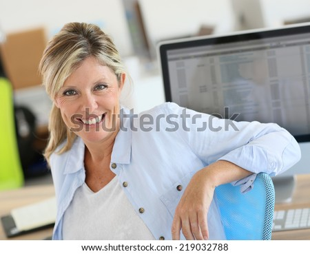 Portrait of cheerful blond woman in office - stock photo