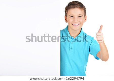 Portrait of  cheerful boy looks out from the  white banner with thumbs up gesture- isolated on white background - stock photo