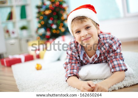Portrait of cheerful boy lying on the floor and looking at camera on Christmas evening - stock photo