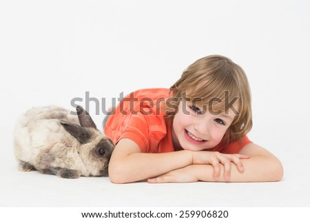 Portrait of cheerful boy with bunny on white background - stock photo