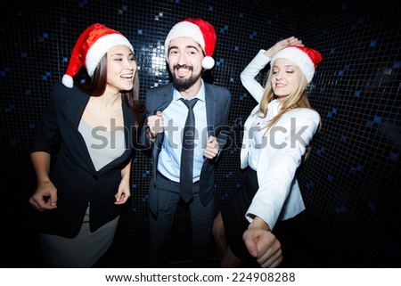 Portrait of cheerful business group in formalwear and Santa caps dancing in night club  - stock photo
