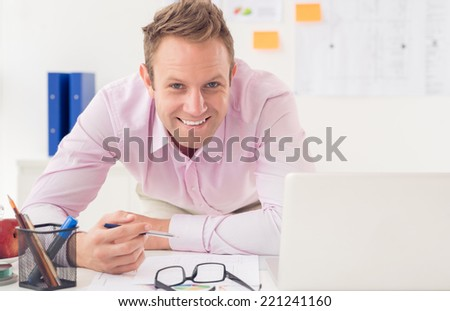 Portrait of cheerful business man working at his table - stock photo