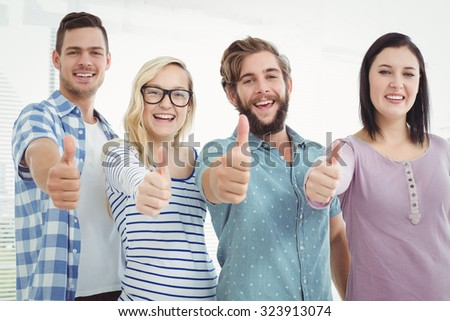 Portrait of cheerful business people with thumbs up at office - stock photo