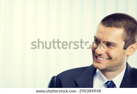 Portrait of cheerful businessman at office, with blank copyspace area for slogan or text - stock photo