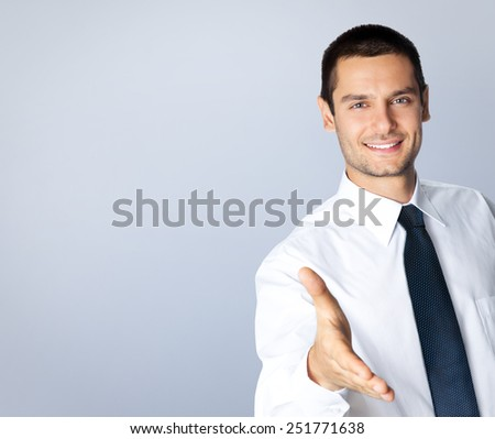 Portrait of cheerful businessman giving hand for handshake, with blank copyspace area for text or slogan, against grey background - stock photo