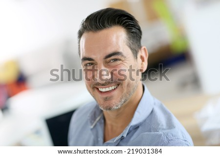Portrait of cheerful businessman in office - stock photo