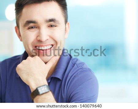Portrait of cheerful businessman looking at camera with smile - stock photo