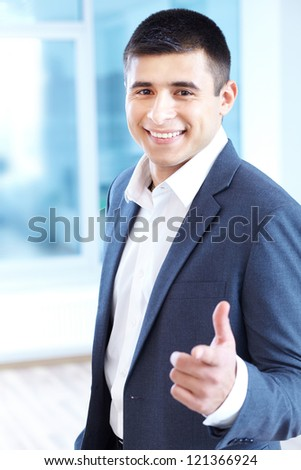 Portrait of cheerful businessman pointing and looking at camera - stock photo