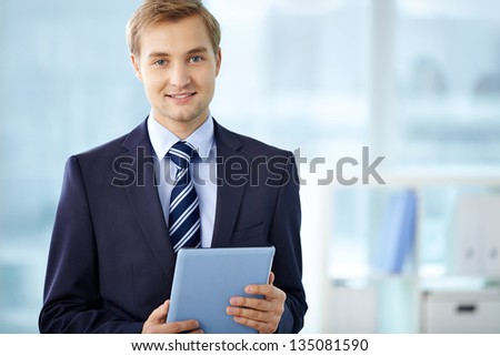 Portrait of cheerful businessman wit hdigital tablet looking at camera - stock photo