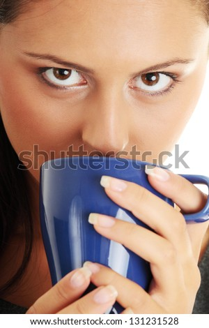 Portrait of cheerful businesswoman holding coffee cup against white background - stock photo
