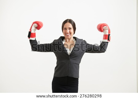 portrait of cheerful businesswoman in formal wear and red boxing gloves looking at camera over light grey background - stock photo