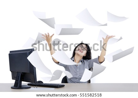 Portrait of cheerful businesswoman looking paper flying over her head, isolated on white background