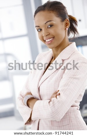 Portrait of cheerful businesswoman standing in office with arms crossed.? - stock photo