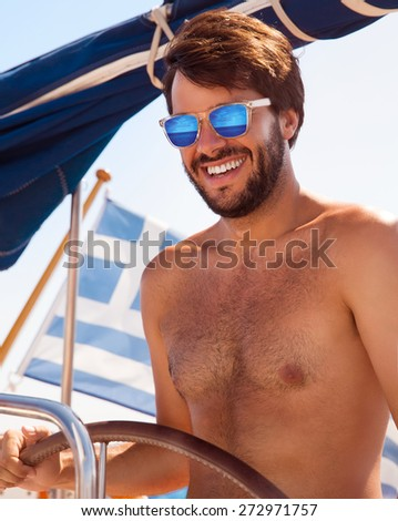 Portrait of cheerful captain behind wheel of luxury sailboat, sexy man wearing stylish sunglasses and enjoy interesting water trip, happy summer vacation concept