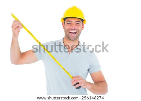 Portrait of cheerful carpenter holding tape measure over white background - stock photo