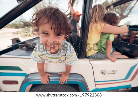 Portrait of cheerful Caucasian boy in an off-road car - stock photo