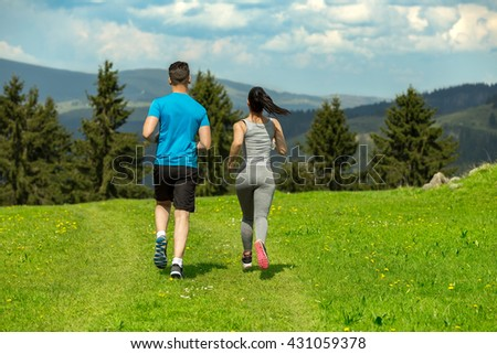 Portrait of cheerful Caucasian couple running outdoors. - stock photo
