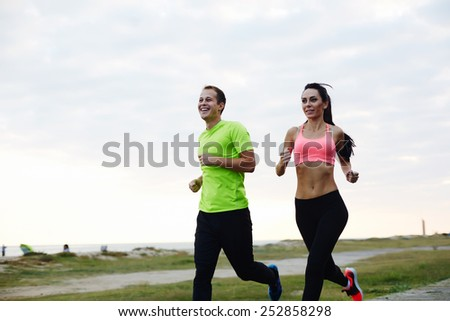 Portrait of cheerful Caucasian couple running outdoors, beautiful young couple working out near the beach jogging in nature - stock photo