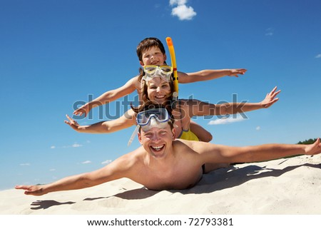 Portrait of cheerful couple and their son lying on sand and looking at camera - stock photo